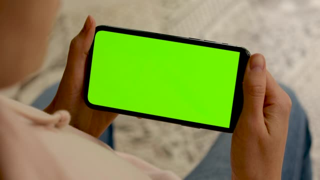 Woman flips through a smartphone with a green screen
