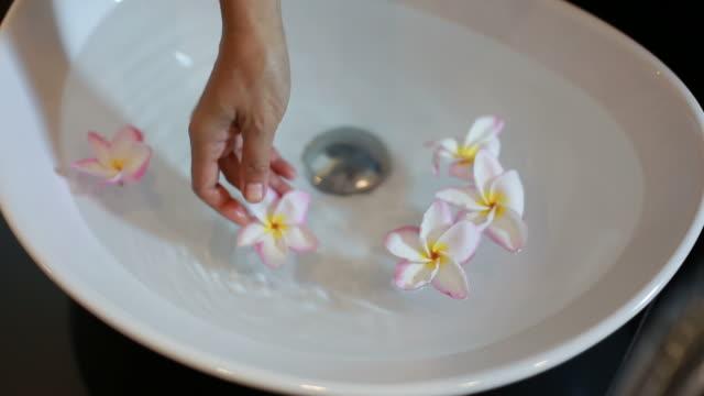 woman floating flower on washbasin video