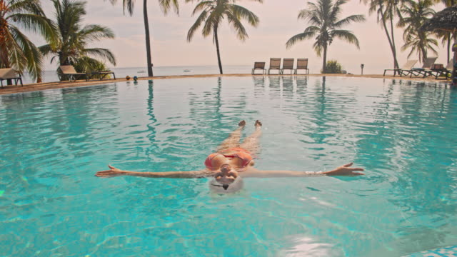 WS Woman floating in the pool of a luxury beach resort