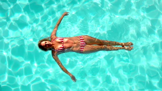 Mujer flotando en la piscina en Cinemagraph - vídeo