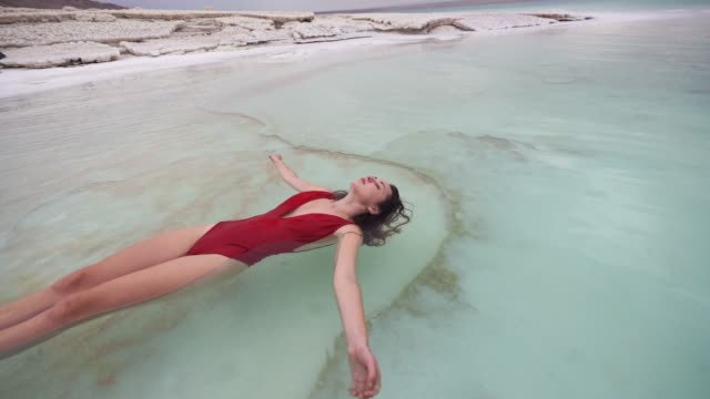 Woman floating on water  in Dead Sea Young Caucasian woman floating on water  in Dead Sea floating on water stock videos & royalty-free footage