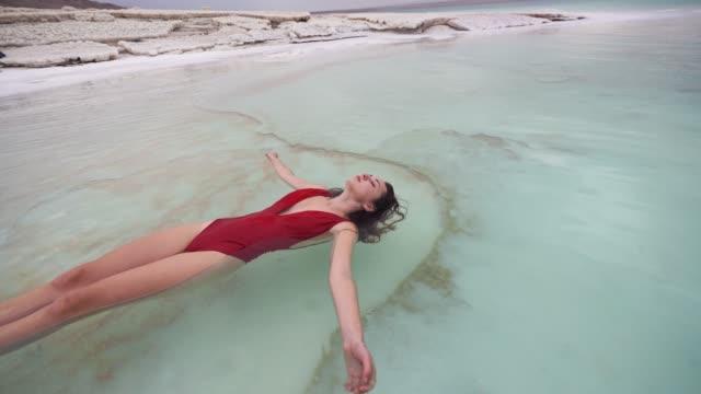 vídeos de stock, filmes e b-roll de mulher flutuando na água, no mar morto - flutuando na água