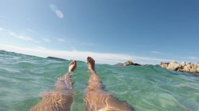Woman floating on water in wavy Adriatic Sea in Dubrovnik, Croatia, personal point of view