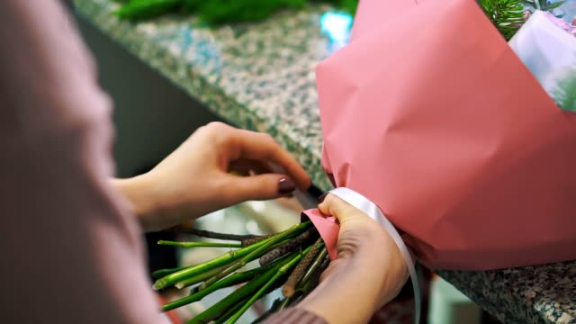 kvinna florist rena fir gren från tall nålar att förbereda buketten. - blomsterarrangemang bildbanksvideor och videomaterial från bakom kulisserna