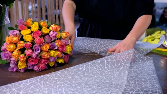 Woman florist is packaging bouquet of roses in craft paper in flower shop.