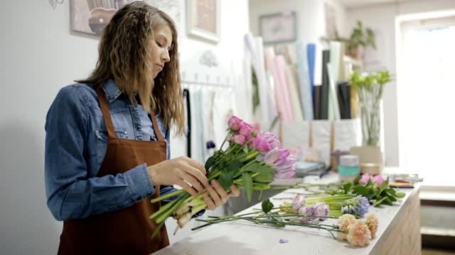 vídeos de stock e filmes b-roll de woman florist make a bouquet of beautiful different flowers - trabalho de design