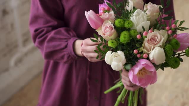 Woman florist makes bouquet of flowers in workshop, close up