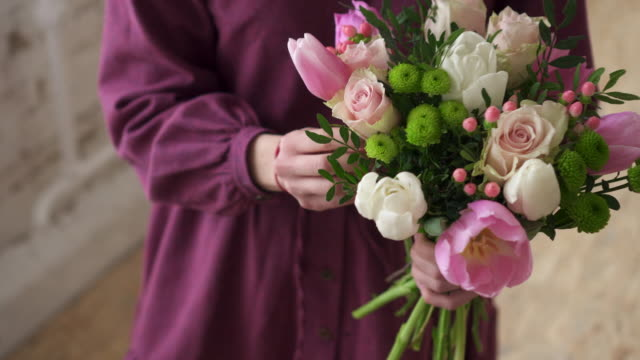 woman florist makes bouquet of flowers in workshop, close up - bouquet video stock e b–roll
