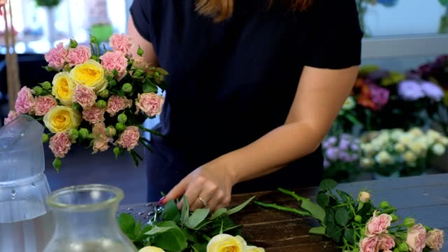 woman florist making flowers bouquet from different sorts roses, hands closeup. - stelo video stock e b–roll