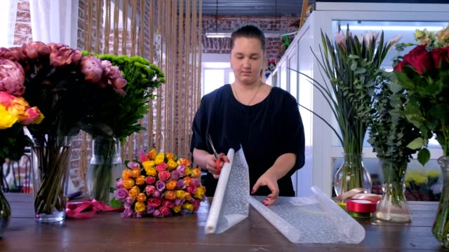 Woman florist works cuts paper sheet to pack flower bouquet in floristic shop.