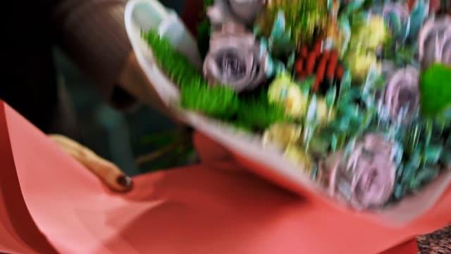 kvinna florist insvept bukett i papper, närbild. - blomsterarrangemang bildbanksvideor och videomaterial från bakom kulisserna