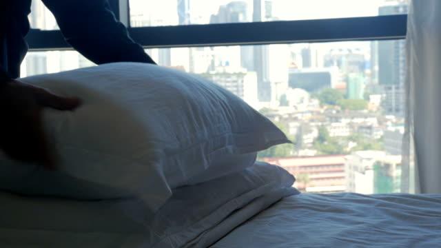 vídeos y material grabado en eventos de stock de mujer esponjar hasta almohadas en una cama con vistas a una ciudad moderna en cámara lenta - almohada