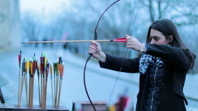 vidéos et rushes de femme concentré frapper la cible avec la flèche. archer femme tire avec un arc en 4k. femme de touristes pratiquant le tir à l'arc. - tir à l'arc