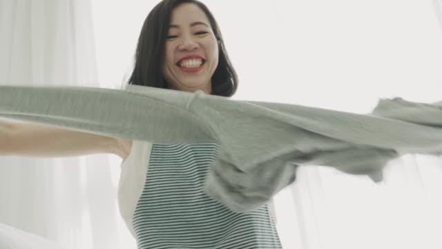 女性の彼女の布を折りたたみ - 楽しい 洗濯点の映像素材/bロール