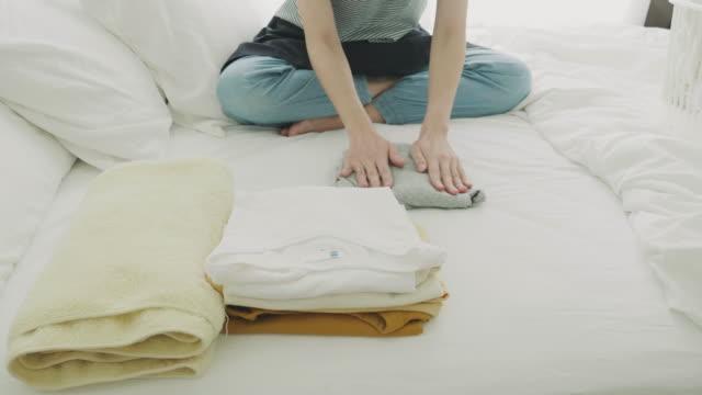 vídeos de stock, filmes e b-roll de mulher dobrar roupa na cama - vestido