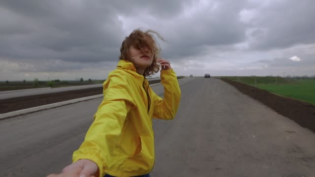 POV, woman follow me holding hands at overcast field video
