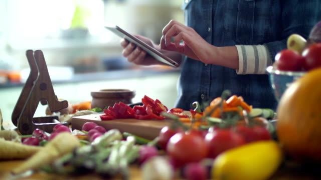 vidéos et rushes de femme, suivant la recette sur tablette numérique dans cuisine - recette