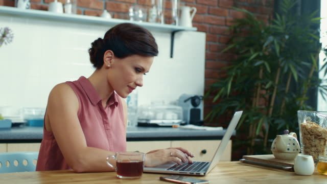 Woman freelancer finishing work on computer. Student girl getting idea at home.