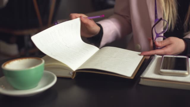 woman freelancer leafing through pages of a diary in a coffee shop. entrepreneur working in cafe. business woman uses paper reminders and schedules. girl writes notes diary, makes business plan - to do list video stock e b–roll