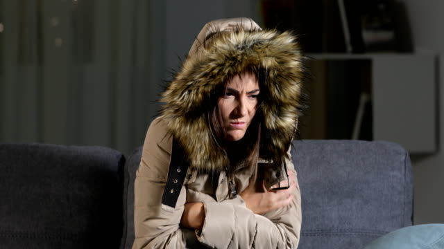 Woman freezing at home in a cold winter