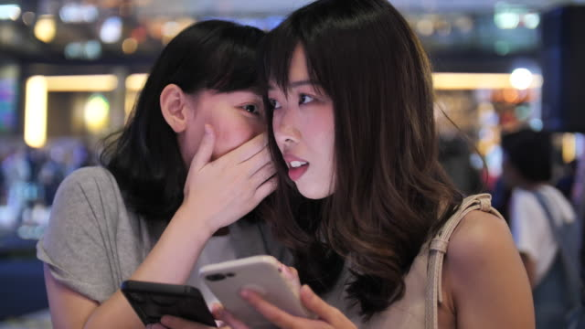 Woman friend gossip to smartphone together