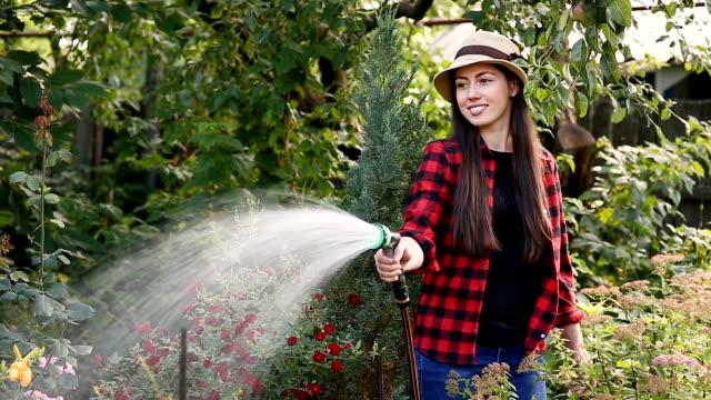 woman gardener watering garden - tubo flessibile video stock e b–roll
