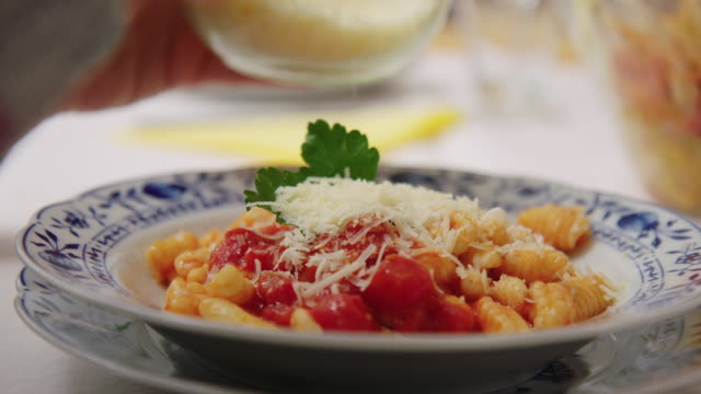 Woman garnishing pasta with grated cheese