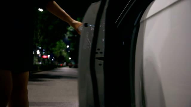 woman get into a car at night - sportello d'auto video stock e b–roll