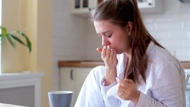 Frau wird kalt und hustet sie trinken heißen Zitronentee um sie besser in das Wohnzimmer zu Hause fühlen zu lassen – Video