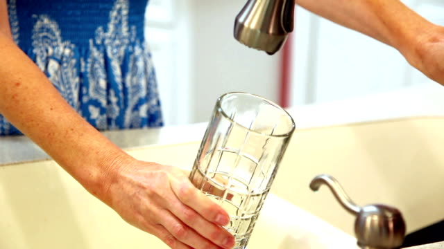 Woman gets drink of clean water in glass. Kitchen sink. Unrecognizable woman pours a glass of clean water into a clear glass from the kitchen sink faucet. Home setting. One mid-adult woman. Clean drinking water, healthy lifestyles concepts. purified water stock videos & royalty-free footage