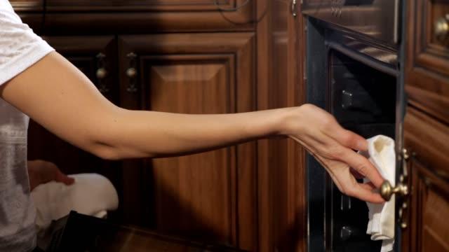 vidéos et rushes de la femme sort du four une plaque de cuisson avec apfelstrudel, plan rapproché de mains. - four