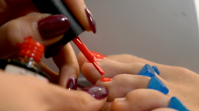 Woman gets professional pedicure with elegant red nail polish video