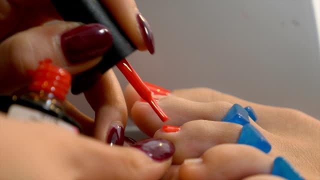 kvinna får professionell pedikyr med elegant rött nagellack - nagellack bildbanksvideor och videomaterial från bakom kulisserna