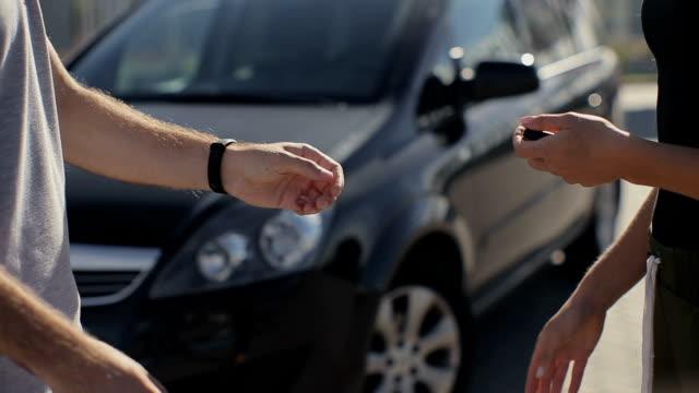 vídeos de stock, filmes e b-roll de mulher recebe a chave do carro de vendedor - satisfeito - comércio fechado - carro novo em segundo plano - vendedor