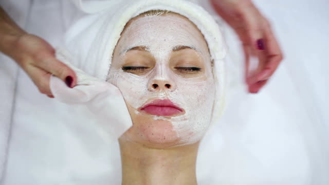 woman getting a facial treatment at the health spa - facial stock videos & royalty-free footage