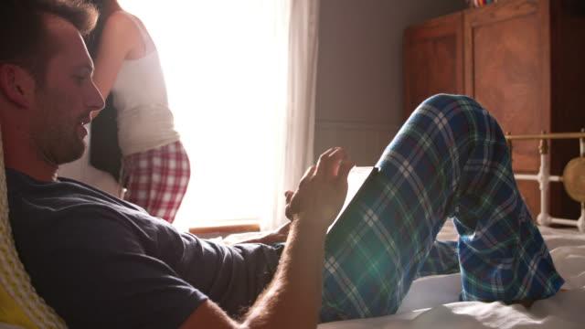 Woman Getting Dressed As Man Uses Digital Tablet In Bedroom video