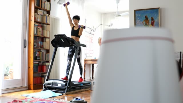 Woman getting fit and doing home training in the living room - video