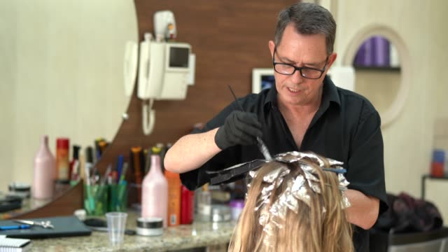 Woman getting her hair dyed at salon Coloring hair salon highlights hair stock videos & royalty-free footage