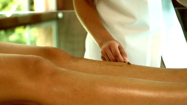 Woman getting her legs waxed by beauty therapist video
