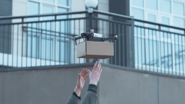 Woman getting her parcel from drone outdoors