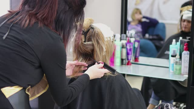 Woman getting highlights in hair salon Blonde woman sitting still when getting highlight done by a hairdresser highlights hair stock videos & royalty-free footage