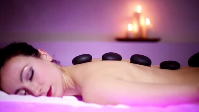 Woman getting hot stone massage in spa salon video