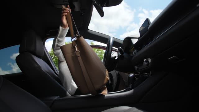woman getting into car and wearing seat belt - entrata video stock e b–roll