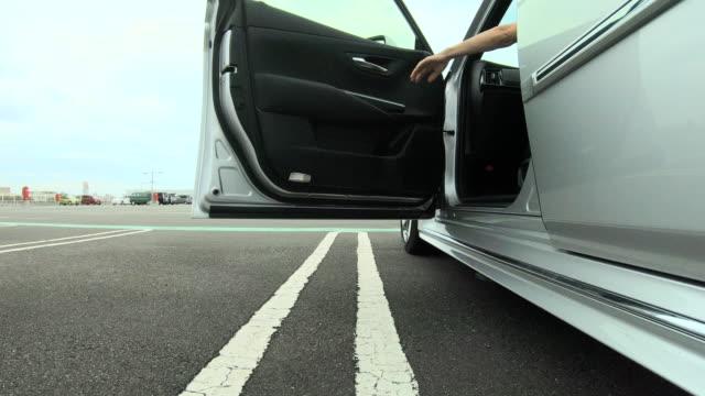 woman getting into the car - sportello d'auto video stock e b–roll