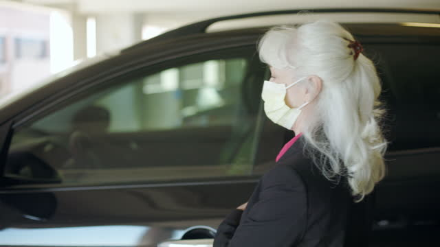 woman getting out of her car putting on  mask
