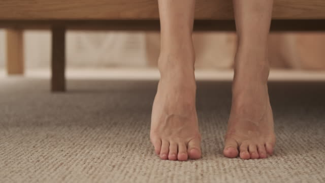 woman getting out of the bed and walking - tappeto video stock e b–roll