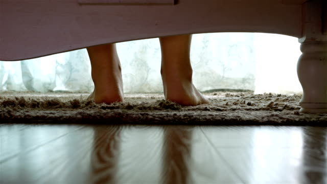 woman getting out of the bed feet touching floor in the morning, camera under the bed - stare in piedi video stock e b–roll
