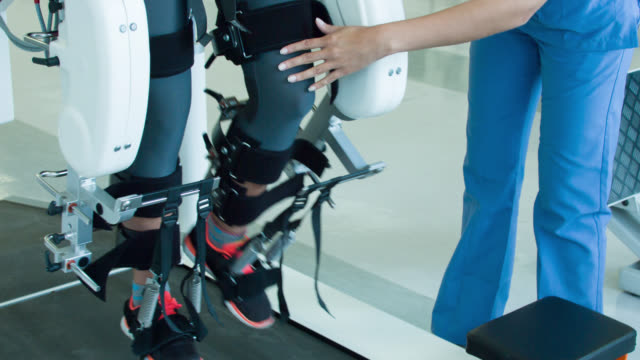 Woman getting physical therapy on a robot machine Woman getting physical therapy on a robot machine to recover movement on her legs at the hospital robot stock videos & royalty-free footage