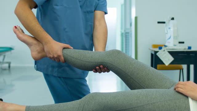 vídeos de stock, filmes e b-roll de mulher recebendo fisioterapia para o tornozelo. - ortopedia