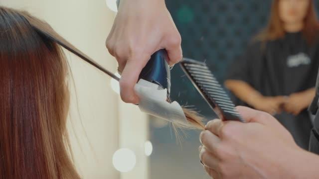 vidéos et rushes de femme se polir les cheveux par le coiffeur au salon de beauté, gros plan - soins capillaires